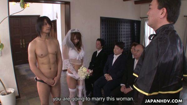 Japonés novia en ropa interior blanca y un velo que le da en la cabeza durante la ceremonia de la boda